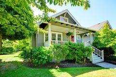 Pequeña casa gris con el pórtico y las verjas blancas. Foto de archivo libre de regalías