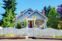 Pequeña casa linda gris con la cerca y las puertas blancas. Imagenes de archivo
