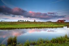 Pequeña casa por el río en la puesta del sol Imagen de archivo