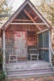 Pequeña casa rústica con las sillas de madera en el pórtico imágenes de archivo libres de regalías