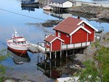 Pequeña casa roja con el barco en Moskenes, Lofoten Fotografía de archivo libre de regalías