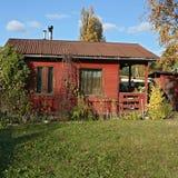 Pequeña casa rojo marrón en jardín Imagen de archivo libre de regalías
