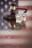 Pequeña casa y mazo en la tabla con la reflexión de la bandera americana Fotografía de archivo libre de regalías