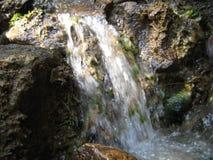Pequeña cascada de la montaña en el pueblo de montaña Foto de archivo libre de regalías