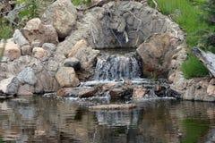 Pequeña cascada que fluye del outcropping rocoso en la charca Imágenes de archivo libres de regalías