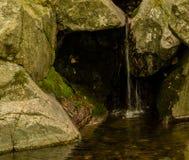 Pequeña cascada que fluye sobre piedras grandes Foto de archivo libre de regalías