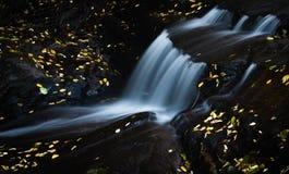 Pequeña cascada rodeada por las hojas de oro en otoño Imagenes de archivo
