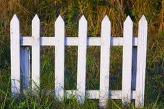 Pequeña cerca de madera blanca baja en hierba Imagen de archivo