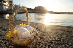 Pequeña cesta con dos huevos de Pascua en el mar doc. en hora de oro fotografía de archivo libre de regalías