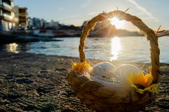 Pequeña cesta con dos huevos de Pascua en el mar doc. en hora de oro imagen de archivo libre de regalías