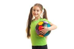 Pequeña chica joven con el balón de fútbol a disposición que sonríe en cámara Foto de archivo