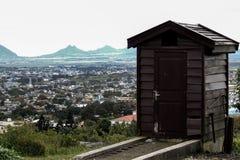 Pequeña choza de madera al borde del campo, ciudad en el fondo Imagen de archivo