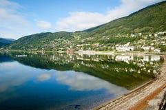 Pequeña ciudad de Noruega que refleja en el agua en un fondo del cielo azul Imagen de archivo