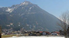 Pequeña ciudad en la parte inferior de la montaña alpina majestuosa, casas privadas, tráfico activo almacen de metraje de vídeo