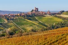 Pequeña ciudad y viñedos amarillos en Piamonte, Italia Imagenes de archivo
