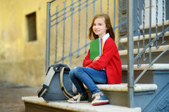 Pequeña colegiala adorable que estudia al aire libre en día brillante del otoño Estudiante joven que hace su preparación Educació Imagen de archivo
