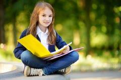 Pequeña colegiala adorable que estudia al aire libre en día brillante del otoño Estudiante joven que hace su preparación Educació Imagen de archivo libre de regalías