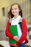Pequeña colegiala adorable que estudia al aire libre en día brillante del otoño Estudiante joven que hace su preparación Educació Foto de archivo