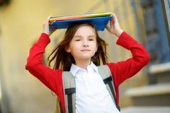 Pequeña colegiala adorable que estudia al aire libre en día brillante del otoño Estudiante joven que hace su preparación Educació Foto de archivo libre de regalías