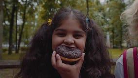 Pequeña colegiala afroamericana divertida que come el buñuelo del chocolate con la emoción feliz en el parque almacen de metraje de vídeo