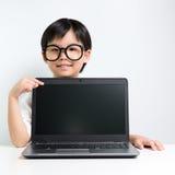 Pequeña colegiala con el ordenador portátil Imágenes de archivo libres de regalías