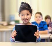 Pequeña colegiala con PC de la tableta sobre sala de clase Imagenes de archivo