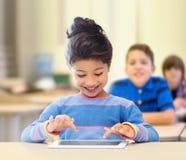 Pequeña colegiala con PC de la tableta sobre sala de clase imágenes de archivo libres de regalías