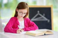 Pequeña colegiala elegante con la pluma y libros que escriben una prueba en una sala de clase Imagen de archivo