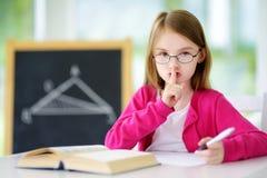 Pequeña colegiala elegante con la pluma y libros que escriben una prueba en una sala de clase Fotos de archivo