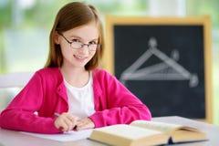 Pequeña colegiala elegante con la pluma y libros que escriben una prueba en una sala de clase Foto de archivo libre de regalías