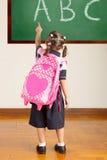 Pequeña colegiala en la sala de clase de la escuela Foto de archivo libre de regalías
