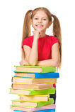 Pequeña colegiala feliz con una pila de libros. Aislado Imágenes de archivo libres de regalías