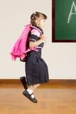 Pequeña colegiala feliz que salta en la sala de clase de la escuela Foto de archivo libre de regalías