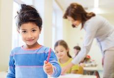 Pequeña colegiala feliz sobre fondo de la sala de clase Imagen de archivo