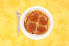 Pequeña comida de la pizza de salchichones en un mantel amarillo Fotos de archivo