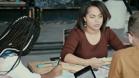Pequeña compañía arquitectónica, reunión creativa del equipo del negocio Grupo de personas joven de la raza mixta que discute pro almacen de metraje de vídeo