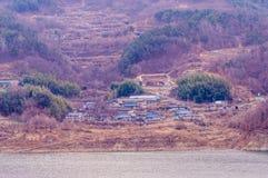 Pequeña comunidad rodeada por los árboles en un valle Imagen de archivo libre de regalías