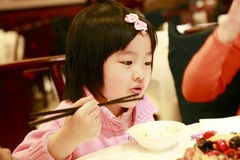 Pequeña consumición asiática de la muchacha Imagenes de archivo