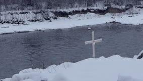 Pequeña cruz instalada en un riverbank de la montaña en Bukovel en invierno en el slo-MES metrajes