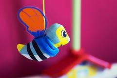 Pequeña ejecución de la abeja sobre cama de bebé Imagen de archivo