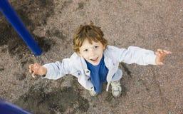 Pequeña ejecución linda del muchacho en el anillo gimnástico Foto de archivo