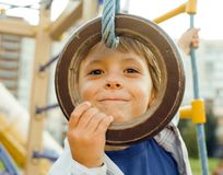 Pequeña ejecución linda del muchacho en el anillo gimnástico Imágenes de archivo libres de regalías
