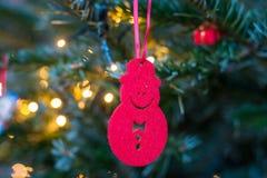 Pequeña ejecución roja del ornamento del muñeco de nieve en un árbol de navidad Fotografía de archivo