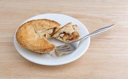Pequeña empanada de manzana en la placa con la sobremesa de la bifurcación Imagenes de archivo