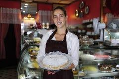 Pequeña empresa: camarera que muestra una torta sabrosa Fotos de archivo