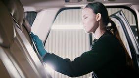 Pequeña empresa - el trabajador de mujer joven está limpiando el interior de un coche metrajes