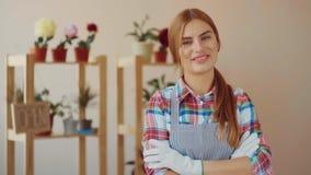 Pequeña empresa Una muchacha en un delantal rayado y una camisa de tela escocesa se coloca en una floristería y dobla sus manos e almacen de video