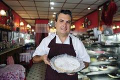 Pequeña empresa: waitr que muestra una torta sabrosa Imagenes de archivo