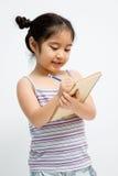 Pequeña escritura asiática hermosa de la muchacha con el lápiz y el cuaderno Imagen de archivo