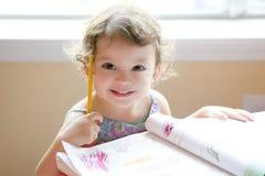 Pequeña escritura de la muchacha del niño en el escritorio de la escuela imágenes de archivo libres de regalías